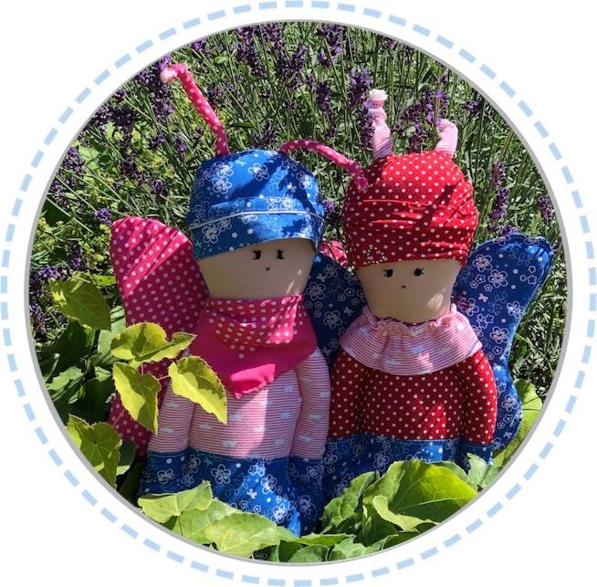 zwei Schmetterlingspuppen rosa-rot-blau im Garten