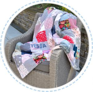 Patchworkdecke bunt rosa hellblau mit Muster ausgebreitet auf Sessel